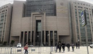 In this file photo, people walk to the main Justice Palace in Istanbul, Wednesday, May 15, 2019, as the trial begins against Metin Topuz, a Turkish employee of the United States Consulate in Istanbul charged with espionage and attempting to overthrow the Turkish government. Mr. Topuz was convicted on June 11, 2020.  (AP Photo/Mehmet Guzel)