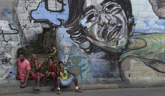 A group of young people rest in a hole in the wall at the Agua Salud neighborhood of Caracas, Venezuela, Wednesday, May 15, 2019. More than 3 million Venezuelans have left their homeland in recent years amid skyrocketing inflation and shortages of food and medicine. U.S. administration officials have warned that 2 million more are expected to flee by the end of the year if the crisis continues in the oil-rich nation. (AP Photo/Martin Mejia)