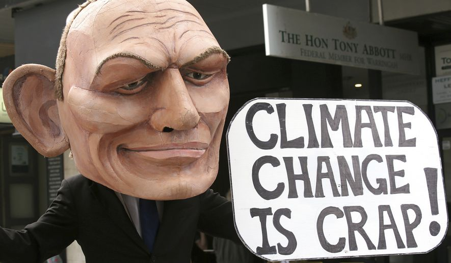 A demonstrator with a giant head in the likeness of former Australian Prime Minister Tony Abbott holds a sign referencing a comment by Abbott made in 2017 belittling the science of climate change, during a student organized protest at in Sydney. (AP Photo/Rick Rycroft, File)