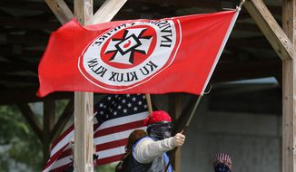 In this Sept. 1, 2018, file photo, a Ku Klux Klan member waves a Klan flag during the Ku Klux Kookout where counterprotests by anti-hate groups were also held at Jaycee Park in Madison, Ind. (Michelle Pemberton/The Indianapolis Star via AP) ** FILE **