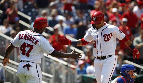 Washington Nationals' Howie Kendrick, left, greets teammate Gerardo Parra after scoring on Parra's two-run home run in the fifth inning of a baseball game against the New York Mets, Thursday, May 16, 2019, in Washington. (AP Photo/Patrick Semansky)