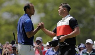 Tiger Woods, left, and Brooks Koepka shake hands after finishing the first round of the PGA Championship golf tournament, Thursday, May 16, 2019, at Bethpage Black in Farmingdale, N.Y. (AP Photo/Seth Wenig)