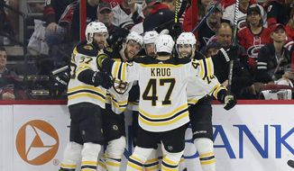 Boston Bruins' Patrice Bergeron (37) David Pastrnak, second from left, Brad Marchand (63), Jake DeBrusk (74) and Torey Krug (47) celebrate Pastrnak's goal against the Carolina Hurricanes during the second period in Game 4 of the NHL hockey Stanley Cup Eastern Conference finals in Raleigh, N.C., Thursday, May 16, 2019. (AP Photo/Gerry Broome) ** FILE **