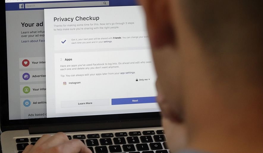 FILE  - In this March 26, 2018, file photo, a man poses for photos in front of a computer showing Facebook ad preferences pages in San Francisco. The state Senate Appropriations Committee failed to advance a bill, by Sen. Hannah-Beth Jackson, D-Santa Barbara, to expand the state's new data privacy law and allow consumers to take companies to court over violations Thursday. (AP Photo/Jeff Chiu, File)
