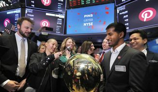 FILE - In this Thursday, April 18, 2019, file photo, Pinterest co-founder and chief product officer Evan Sharp, left, and fellow co-founder & CEO Ben Silbermann, right, watch as company communications manager Enid Hwang rings a ceremonial bell when their IPO begins trading on the New York Stock Exchange floor. Pinterest, fresh off its initial public offering, is reporting a smaller loss in the first quarter, boosted by higher revenue, but its outlook was below expectations and shares slumped in after-hours trading. (AP Photo/Richard Drew, File)