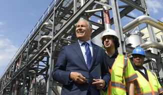 Democratic Presidential candidate Washington Gov. Jay Inslee, left, talks with James Fotouhi, center, and Chester Hunter, right, during a tour of the Blue Plains Advanced Wastewater Treatment Plant in Washington, Thursday, May 16, 2019, during an event where he unveiled part of his plan to defeat climate change. (AP Photo/Susan Walsh)