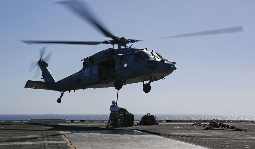 In this Friday, May 10, 2019 photo released by the U.S. Navy, logistics specialists attach cargo to an MH-60S Sea Hawk helicopter on the flight deck of the Nimitz-class aircraft carrier USS Abraham Lincoln in the  Persian Gulf. The  aircraft carrier strike group is being deployed to the Persian Gulf to counter an alleged but still-unspecified threat from Iran. (Mass Communication Specialist 3rd Class Amber Smalley, U.S. Navy via AP)