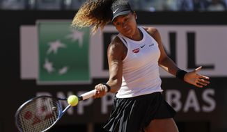Japan's Naomi Osaka returns the ball during her match against Slovakia's Dominika Cibulkova at the Italian Open tennis tournament, in Rome, Thursday, May, 16, 2019. (AP Photo/Gregorio Borgia)