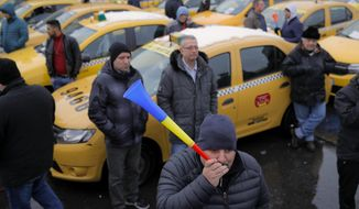 FILE - In this Wednesday, Feb. 13, 2019, file photo a taxi driver blows into a horn during a protest against ride hailing services in Bucharest, Romania. The Romanian government has issued an emergency decree ramping up steep fines for drivers of ride-hailing services like Uber and Taxify. The decree taking effect Thursday, May 16, 2019 fines drivers transporting people in their car without a valid taxi license up to $1,175 (1,050 euros) already from the first offense. Previously, drivers were fined only after repeated offenses. (AP Photo/Vadim Ghirda, File)