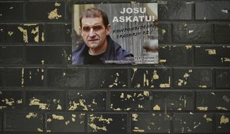 A poster with the face of Basque separatist militant Josu Ternera is attached to a wall in his home town of Ugao-Miraballes, Spain, Thursday, May 16, 2019. The most wanted member of the Basque separatist militant group ETA who had been on the run for 17 years was finally caught by police on Thursday May 16, 2019 in the French Alps. Jose Antonio Urruticoetxea Bengoetxea, known by the alias Josu Ternera, was a longtime chief of ETA and connected to some of its bloodiest episodes. The poster has a message written in the Basque language saying 'No solution to the solution' while calling for a protest gathering in the town this evening supporting him. (AP Photo/Alvaro Barrientos)