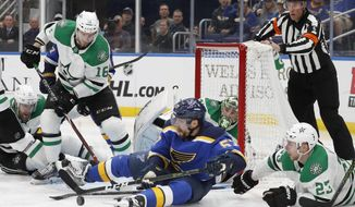 St. Louis Blues left wing David Perron (57) reaches for the puck after falling to the ice with Dallas Stars defenseman Esa Lindell (23), of Finland, during the second period in Game 5 of an NHL second-round hockey playoff series Friday, May 3, 2019, in St. Louis. (AP Photo/Jeff Roberson)