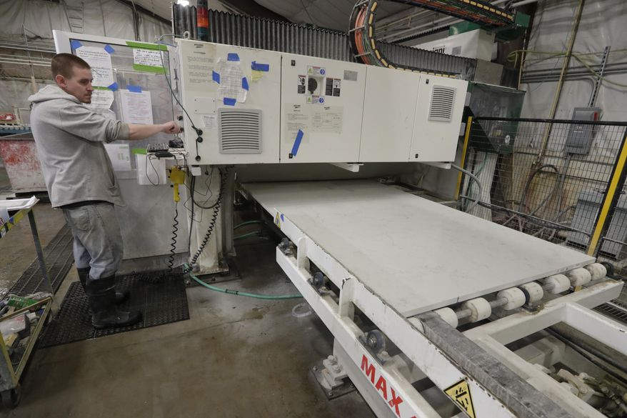 A worker begins production of a kitchen countertop that is being cut from imported quartz slabs from China in the production facility at Marble Uniques in Tipton, Ind., Friday, May 3, 2019. The Trump administration's trade warriors are fighting obscure battles over laminated woven sacks from Vietnam, for example, olives from Spain and rubber bands from Thailand. The International Trade Commission in Washington this week will provide an arena for combat over kitchen and bathroom countertops _ or at least the imported quartz slabs that many of them come from. (AP Photo/Michael Conroy)