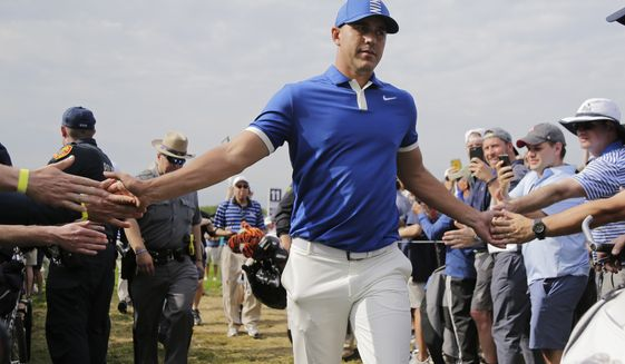 Brooks Koepka greets spectators as he walks to the 12th tee during the second round of the PGA Championship golf tournament, Friday, May 17, 2019, at Bethpage Black in Farmingdale, N.Y. (AP Photo/Seth Wenig)