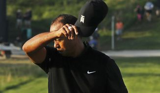 Tiger Woods removes his hat after finishing the second round of the PGA Championship golf tournament, Friday, May 17, 2019, at Bethpage Black in Farmingdale, N.Y. (AP Photo/Andres Kudacki)