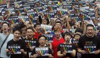 Same-sex marriage supporters gather outside the Legislative Yuan in Taipei, Taiwan, Friday, May 17, 2019. Taiwan's Constitutional Court are scheduled to decide Friday on legalizing same-sex marriage, marking a potential first in Asia. The signs read  ''Vote Can't Be Defeated.'' (AP Photo/Chiang Ying-ying)