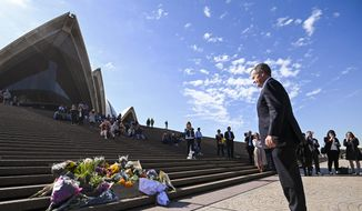 Australian Labor Party leader Bill Shorten, right, pauses after placing a floral tribute to the late former Australian Prime Minster Bob Hawke at the Opera House in Sydney, Friday, May 17, 2019. A federal election will be held in Australian on Saturday May 18, 2019. (Lukas Coch/AAP Image via AP)