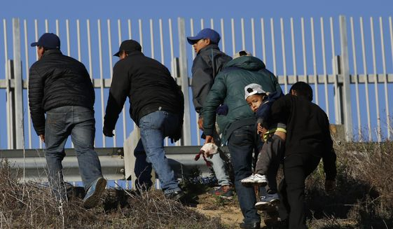 In this Dec. 12, 2018, file photo, Honduran migrants, one carrying a child, who plan to turn themselves over to U.S. border patrol agents, walk up the embankment after climbing over the U.S. border wall from Playas de Tijuana, Mexico in Tijuana, Mexico. The group crossed to apply for asylum. A federal judge on Friday, May 17, 2019, in California will consider a challenge to President Donald Trump's plan to tap billions of dollars from the Defense and Treasury departments to build his prized border wall with Mexico. (AP Photo/Moises Castillo, File)