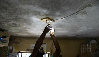 In this April 16, 2019 photo, Johny Legagneur charges a light bulb for a client at his shop in Petion-Ville, Haiti. Johny uses an inverter and generator to charge laptops, smartphones and rechargeable bulbs for a fee. Haiti's Bureau of Monetization of Development Aid Programs, started to buy oil on the global market, but it has now said that it has run out of operating funds and stopped regularly delivering fuel needed by power station operators to keep the lights on. ( AP Photo/Dieu Nalio Chery)