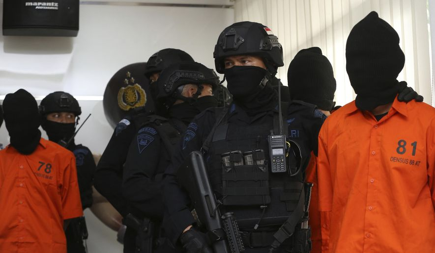 Indonesian Special Detachment 88 anti-terror police unit escorts terror suspect during a press conference at in Jakarta, Indonesia, Friday, May 17, 2019. Police say they have arrested suspected militants following a tipoff about a possible attack during the announcement of presidential election results next week. (AP Photo/Achmad Ibrahim)