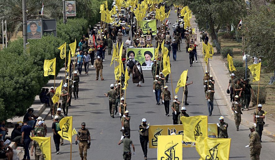 """FILE - In this June 8, 2018 file photo, Iraqi Popular Mobilization Forces march as they hold their flag and posters of Iraqi and Iranian Shiites spiritual leaders during """"al-Quds"""" or Jerusalem Day, in Baghdad, Iraq. When U.S. Secretary of State Mike Pompeo sat down with Iraqi officials in Baghdad earlier this month as tensions were mounting between the U.S. and Iran, he delivered a nuanced message: If you're not going to stand with us, stand aside. (AP Photo/Hadi Mizban, File)"""
