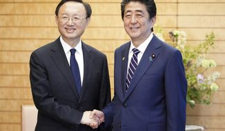 Chinese State Councilor Yang Jiechi, left, and Japanese Prime Minister Shinzo Abe, right, shake hands at Abe's official residence in Tokyo Friday, May 17, 2019. (AP Photo/Eugene Hoshiko, Pool)