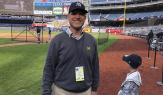 """Michigan football coach Jim Harbaugh and his son, Jack, stand on the field at Yankee Stadium before the New York Yankees' baseball game against the Tampa Bay Rays on Friday, May 17, 2019, in New York. Shaking hands and posing for photos on the field during batting practice, Harbaugh wore a Yankees cap, a Michigan sweater vest and — of course — a crisp pair of khakis. He says he and his father had never been to Yankee Stadium before and it's a """"bucket list"""" trip for them. Harbaugh, a lifelong baseball fan, grew up rooting for the Detroit Tigers while his father was an assistant coach under Bo Schembechler at Michigan. (AP Photo/Mike Fitzpatrick)"""