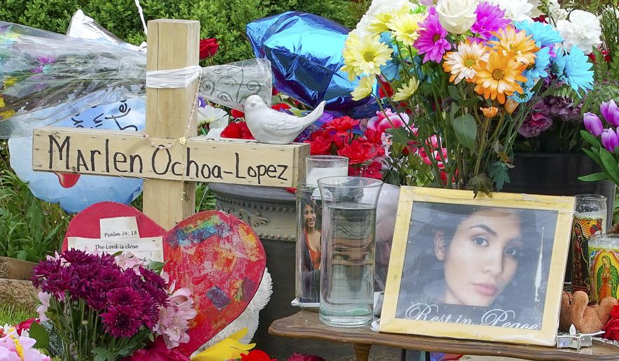 A memorial of flowers, balloons, a cross and photo of victim Marlen Ochoa-Lopez, are displayed on the lawn, Friday, May 17, 2019 in Chicago, outside the home where Ochoa-Lopez was murdered last month. Assistant State's Attorney James Murphy says a pregnant Ochoa-Lopez, who was killed and whose baby was cut from her womb, was strangled while being shown a photo album of the late son and brother of her attackers. (AP Photo/Teresa Crawford)