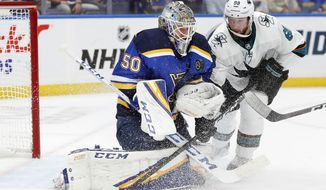 St. Louis Blues goaltender Jordan Binnington (50) protects the puck as San Jose Sharks center Melker Karlsson (68), of Sweden, closes in during the second period in Game 4 of the NHL hockey Stanley Cup Western Conference final series Friday, May 17, 2019, in St. Louis. (AP Photo/Jeff Roberson)