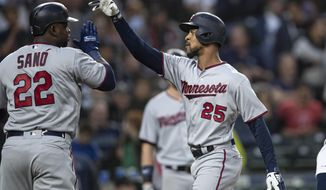 Minnesota Twins' Byron Buxton, right, is congratulated by Miguel Sano after hitting a three-run home run off of starting pitcher Erik Swanson that scored Sano and Jason Castro during the fourth inning of a baseball game, Thursday, May 16, 2019, in Seattle. (AP Photo/Stephen Brashear)