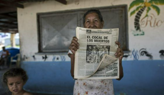 A woman shows a 2012 publication of a local newspaper carrying the story of the 1967 Cuban guerrilla operation in Machurucuto, Venezuela, Sunday, May 5, 2019. Fifty-two years ago this month an expeditionary force of 12 guerrillas departed from the communist-run island and days later landed in this sleepy fishing village with the goal of spreading Fidel Castro's revolution to South America. (AP Photo/Rodrigo Abd)