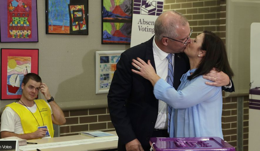 Australian Prime Minister Scott Morrison, center, kisses his wife, Jenny, after casting his ballot in a federal election in Sydney, Australia, Saturday, May 18, 2019. Political leaders continued frenetic 11th-hour campaigning as Australians vote on Saturday in an election likely to deliver the nation's sixth prime minister in as many years. (AP Photo/Rick Rycroft)