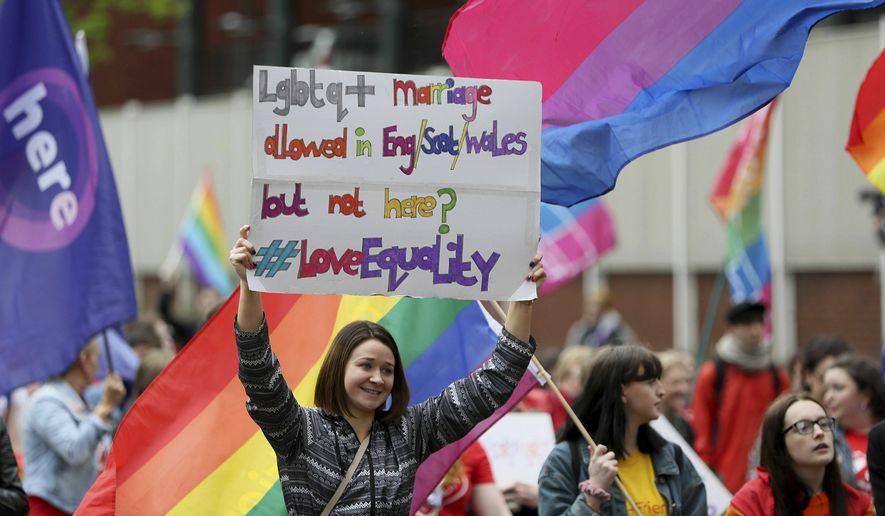 People take part in a march demanding same sex marriage in Northern Ireland, in Belfast city centre, Northern Ireland, Saturday May 18, 2019. Thousands marched in Northern Ireland to demand that the regions leaders permit same-sex marriage. Demonstrators want same sex couple to be treated the same way in Northern Ireland as they are in the rest of the UK, where same sex marriage is legal.  (Brian Lawless/PA via AP)