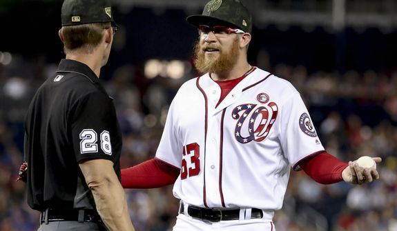 Washington Nationals relief pitcher Sean Doolittle speaks with umpire Jim Wolf (28) after Chicago Cubs manager Joe Maddon argues over his pitching mechanics during the ninth inning of a baseball game, Saturday, May 18, 2019, in Washington. The Washington Nationals won 5-2. (AP Photo/Andrew Harnik)