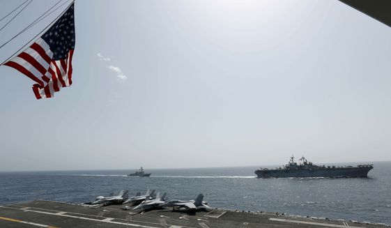 """In this Friday, May 17, 2019, photo, released by the U.S. Navy, the amphibious assault ship USS Kearsarge, right, and the Arleigh Burke-class guided-missile destroyer USS Bainbridge, left, are seen from the Nimitz-class aircraft carrier USS Abraham Lincoln as they sail in the Arabian Sea. Commercial airliners flying over the Persian Gulf risk being targeted by """"miscalculation or misidentification"""" from the Iranian military amid heightened tensions between the Islamic Republic and the U.S., American diplomats warned Saturday, May 19, 2019, even as both Washington and Tehran say they don't seek war. (Mass Communication Specialist Seaman Michael Singley, U.S. Navy via AP)"""