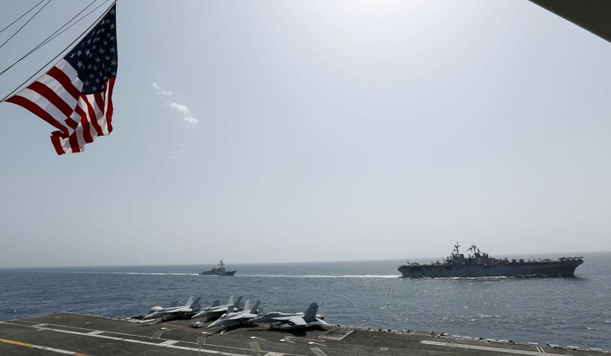 "In this Friday, May 17, 2019, photo, released by the U.S. Navy, the amphibious assault ship USS Kearsarge, right, and the Arleigh Burke-class guided-missile destroyer USS Bainbridge, left, are seen from the Nimitz-class aircraft carrier USS Abraham Lincoln as they sail in the Arabian Sea. Commercial airliners flying over the Persian Gulf risk being targeted by ""miscalculation or misidentification"" from the Iranian military amid heightened tensions between the Islamic Republic and the U.S., American diplomats warned Saturday, May 19, 2019, even as both Washington and Tehran say they don't seek war. (Mass Communication Specialist Seaman Michael Singley, U.S. Navy via AP)"