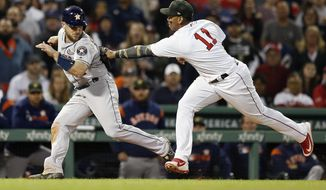Boston Red Sox's Rafael Devers (11) tags out Houston Astros' Max Stassi in a rundown after a line-out by Alex Bregman during the seventh inning of a baseball game in Boston, Saturday, May 18, 2019. (AP Photo/Michael Dwyer)