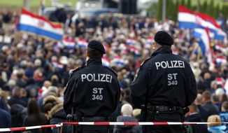 Austrian police officers observe as thousands of mourners gather for a liturgical service in Bleiburg, Austria, Saturday, May 18, 2019. Thousands of Croatian far-right supporters have gathered in a field in southern Austria to commemorate the massacre of pro-Nazi Croats by communists at the end of World War II. (AP Photo/Darko Bandic)