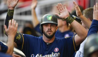 Milwaukee Brewers' Mike Moustakas celebrates in the dugout after scoring on a Jesus Aguilar single to center field during the first inning of the team's baseball game against the Atlanta Braves, Saturday, May 18, 2019, in Atlanta. (AP Photo/John Amis)