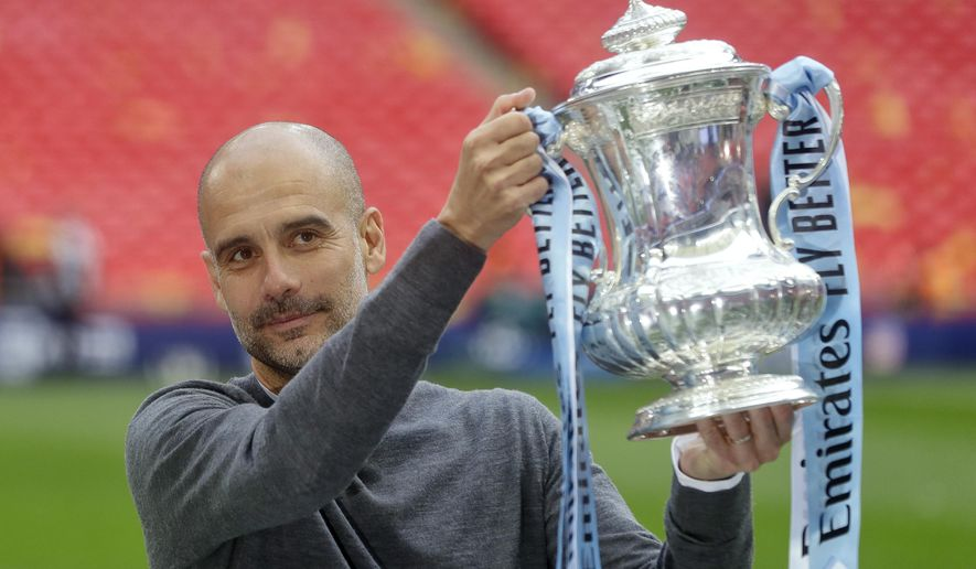 Manchester City's manager Pep Guardiola poses with the trophy after the English FA Cup Final soccer match between Manchester City and Watford at Wembley stadium in London, Saturday, May 18, 2019. (AP Photo/Kirsty Wigglesworth)