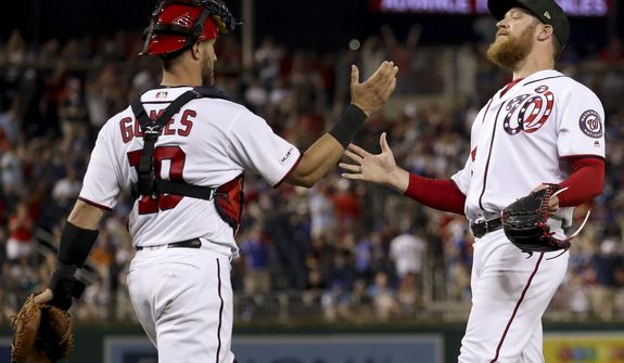 Washington Nationals catcher Yan Gomes (10) and Washington Nationals relief pitcher Sean Doolittle, right, celebrate after the Nationals defeated the Chicago Cubs 5-2 in a baseball game Saturday, May 18, 2019, in Washington. (AP Photo/Andrew Harnik)