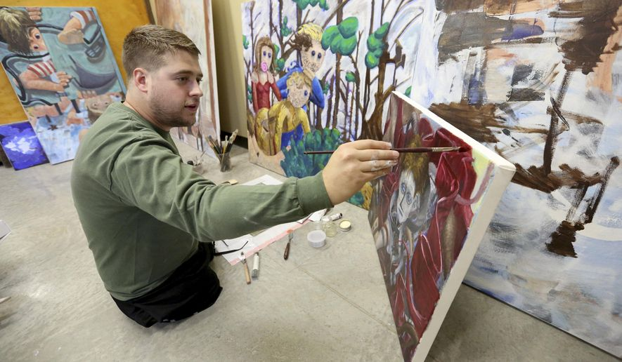 Christopher Billmyer works on an oil painting at Schmid Innovation Center in Dubuque on Thursday, May 9, 2019. Billmyer is a Dubuque native who lost both his legs in an explosion in Aghanistan. After graduating from University of Iowa this spring, he will return to Dubuque to open an art studio. (Jessica Reilly/Telegraph Herald via AP)