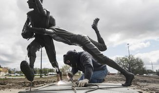 Johnny Jeffrey welds a statue to a base at the former Prenger's location in Norfolk, Neb., Thursday, May 9, 2019. (Jake Wragge/The Daily News via AP)