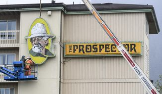 In this Wednesday, May 8, 2019 photo a Juneau Electric crew takes down signage at The Prospector hotel in Juneau, Alaska. As the large, iconic yellow signs came down from the side of the Ramada by Wyndham hotel in Juneau, formerly known as the Prospector Hotel, Jessica Meacham watched with mixed emotions. (Michael Penn/Juneau Empire via AP)