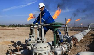 FILE - In this Thursday, Jan. 12, 2017 file photo, a worker operates valves in Nihran Bin Omar field north of Basra, Iraq. An Iraqi oil official says employees of energy giant Exxon Mobil have started evacuating an oil field in the southern province of Basra, amid rising tensions between the United States and Iran. The first group left two days ago and another batch left early Saturday May 18, 2019. (AP Photo/Nabil al-Jurani, File)