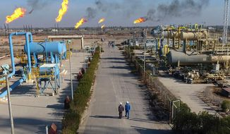 In this Thursday, Jan. 12, 2017, photo, workers walk in the Nihran Bin Omar field north near Basra, Iraq. An Iraqi oil official says employees of energy giant Exxon Mobil have started evacuating an oil field in the southern province of Basra, amid rising tensions between the United States and Iran. The first group left two days ago and another batch left early Saturday, May 18, 2019. (AP Photo/Nabil al-Jurani) **FILE**