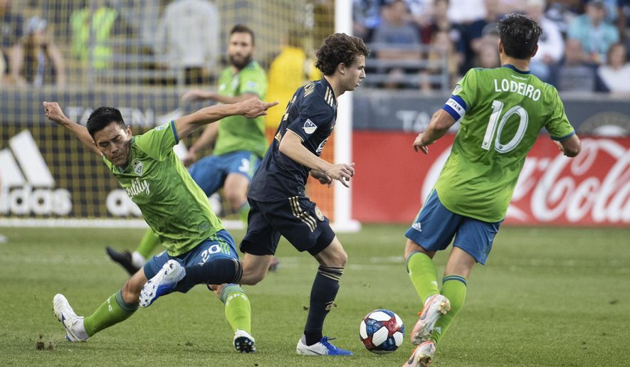 Philadelphia Union's Brenden Aaronson, center, slips between Seattle Sounders' Kim Kee-Hee, left, and Nicolas Lodeiro with the ball during the first half of an MLS soccer match Saturday, May 18, 2019, in Chester, Pa. (AP Photo/Chris Szagola)