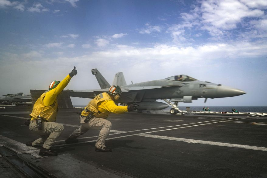 """In this Thursday, May 16, 2019 photo released by the U.S. Navy, Lt. Nicholas Miller, from Spring, Texas, and Lt. Sean Ryan, from Gautier, Miss., launch an F-18 Super Hornet from the deck of the USS Abraham Lincoln aircraft carrier in the Arabian Sea. On Saturday, May 18, 2019, U.S. diplomats warned that commercial airliners flying over the wider Persian Gulf faced a risk of being """"misidentified"""" amid heightened tensions between the U.S. and Iran. (Mass Communication Specialist 3rd Class Jeff Sherman, U.S. Navy via AP)"""