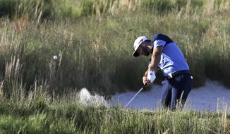 Dustin Johnson hits out of a bunker on the 18th hole during the third round of the PGA Championship golf tournament, Saturday, May 18, 2019, at Bethpage Black in Farmingdale, N.Y. (AP Photo/Charles Krupa)