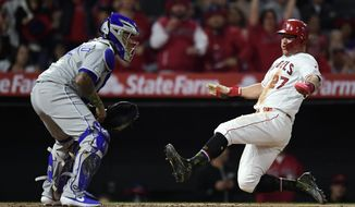 Los Angeles Angels' Mike Trout, right, scores on a single by Albert Pujols as Kansas City Royals catcher Martin Maldonado waits for the ball during the seventh inning of a baseball game Friday, May 17, 2019, in Anaheim, Calif. (AP Photo/Mark J. Terrill)