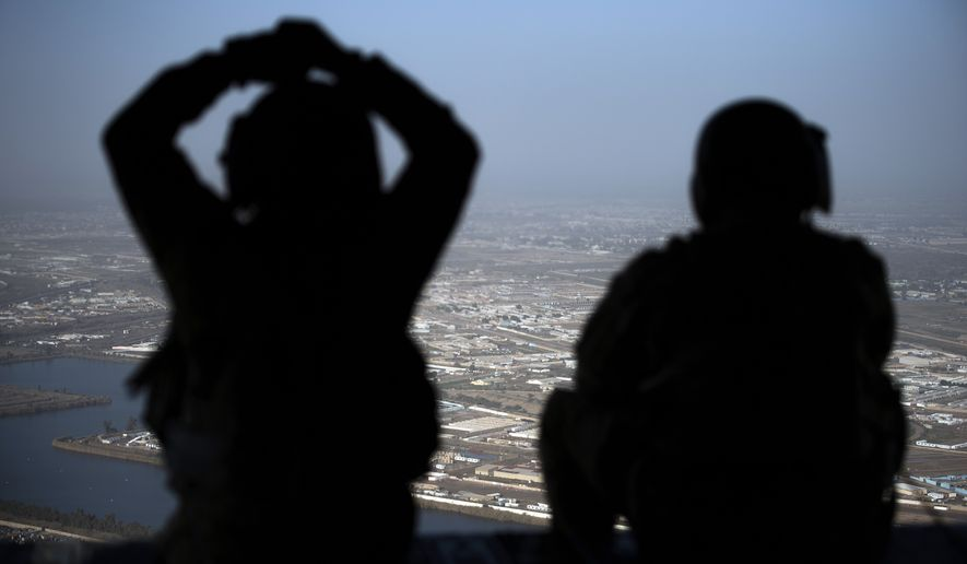 U.S. Army helicopter crew members look out of their Chinook helicopter as they fly from the U.S. Embassy to Baghdad International airport, following the helicopter of Secretary of State Mike Pompeo, over Baghdad, Iraqi, Wednesday, Jan. 9, 2019.   (Andrew Caballero-Reynolds/Pool Photo via AP)